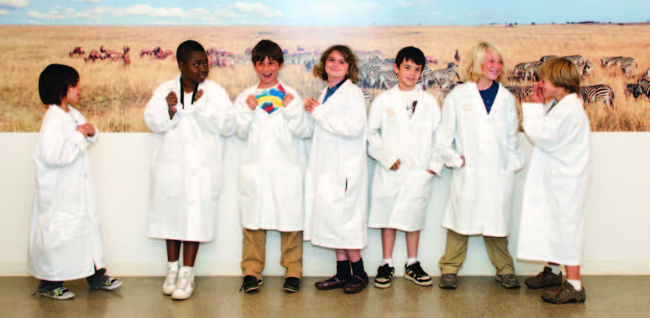 Group of cute kids in white lab coats at the Academy