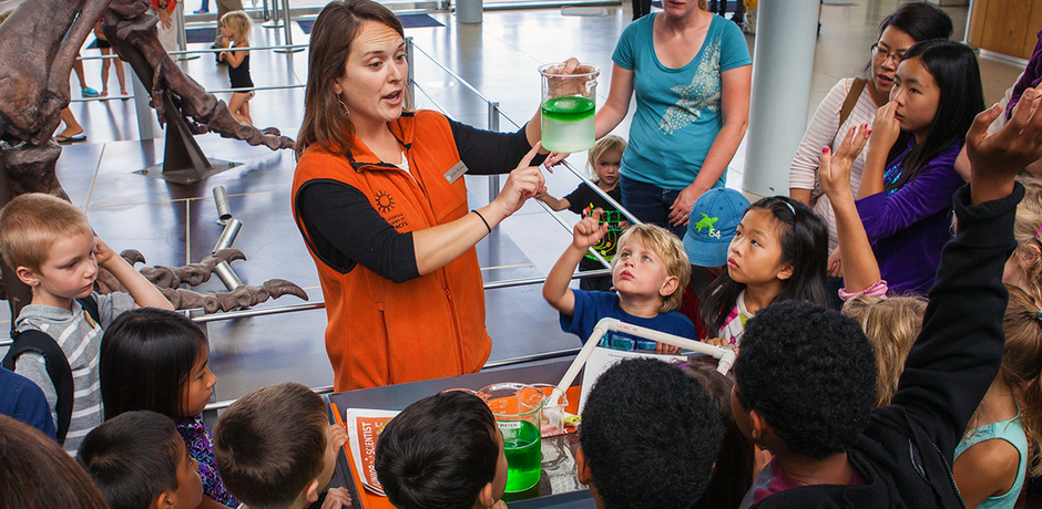 A docent leads a hands-on science experiment to a group of curious school kids