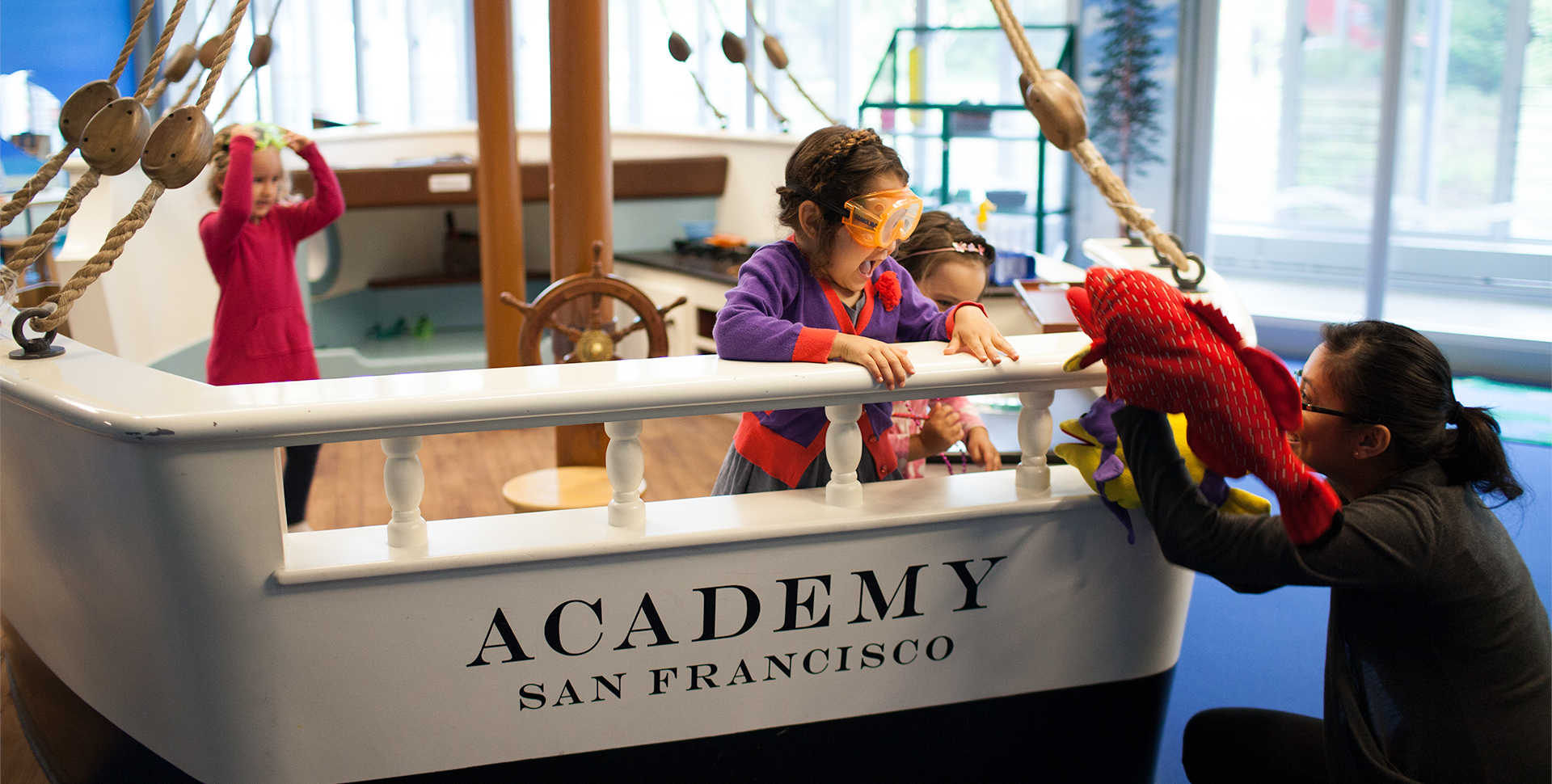 Young children play aboard a pint-sized replica of the H.M.S. Academy.