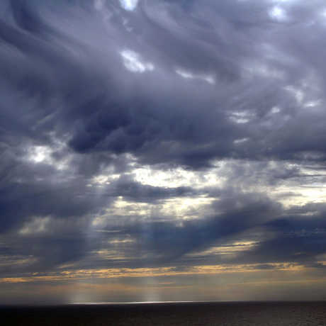 Mammatus clouds and crepuscular rays over the Pacific Ocean.