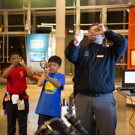 California Academy of Sciences staff member demonstrates proper magnifying glass technique to school kids