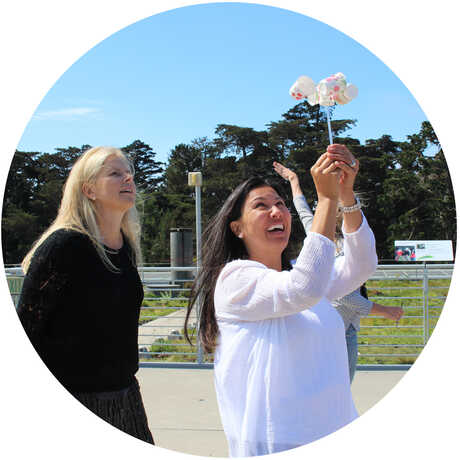2 female educators experiment with an anemometer on Academy Living Roof