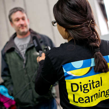 A teenager in the Digital Learning program interviews someone for a project.