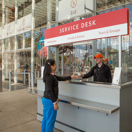 A visitor purchasing tickets in front of California Academy of Sciences.