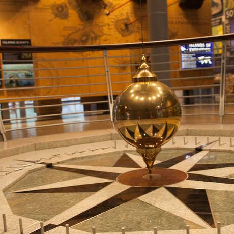 Closeup of large, golden ball of the Focault Pendulum.