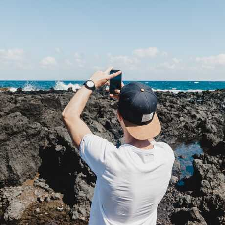 A man stands on a rocky shoreline with a cellphone