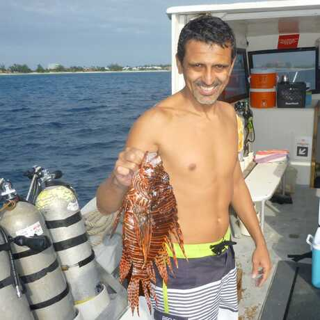 Photo of Luiz Rocha with lionfish in Cayman Islands