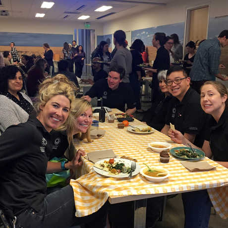 A group of veggie-loving staff enjoy a vegetarian community potluck at work.
