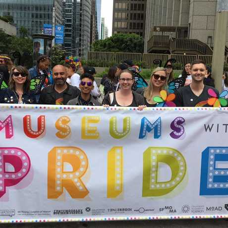 Pride club members march with a colorful banner