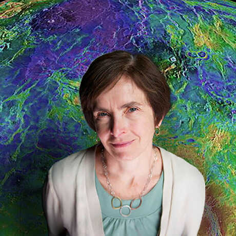Suzanne Smrekar stands before a color-coded, topographical map of Venus.