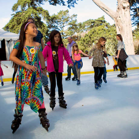 Girl in tie-dye ice skates with friends at Academy's Holiday Ice Rink