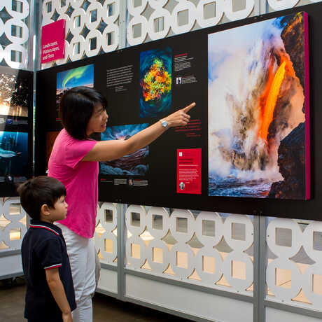 Mother and son look at photos on exhibit in BigPicture