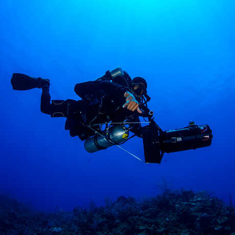 Dive Safety Officer Mauritius Bell descends into a brilliant blue canyon off Grand Cayman