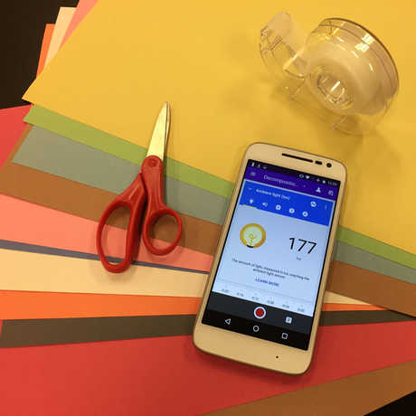 A smartphone, scissors, and scotch tape atop multicolored construction paper