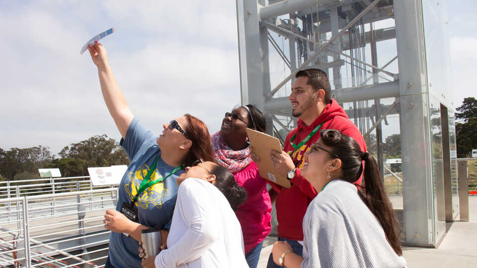 Science Action Club educators compare the sky with a paint chip on Academy Living Roof