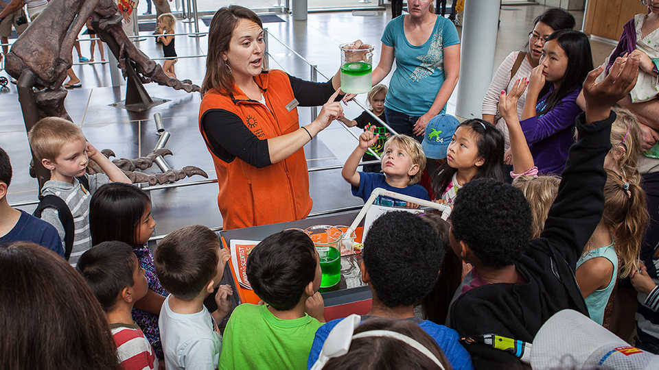 A docent teaches a group of school children chemistry in the main lobby of the California Academy of Sciences.
