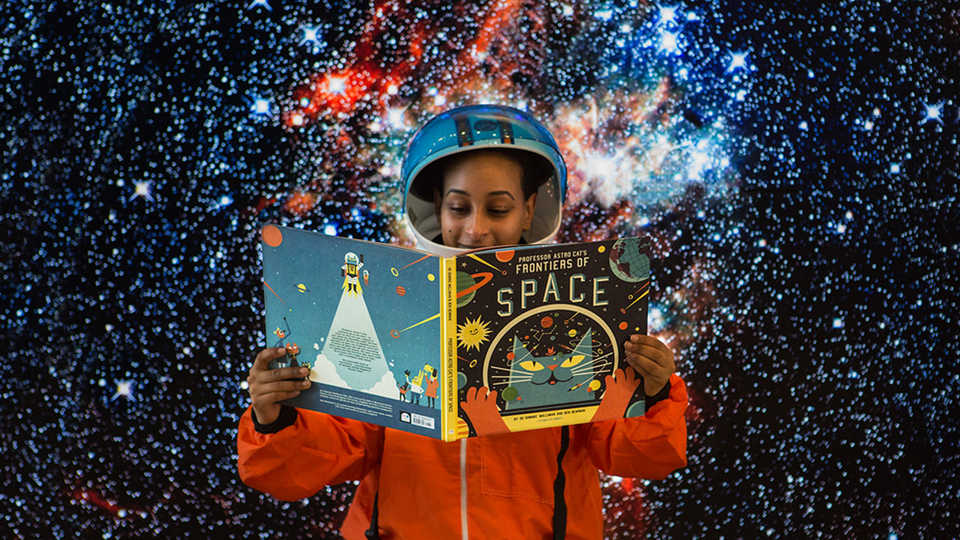Astronaut holding storybook for interstellar story time