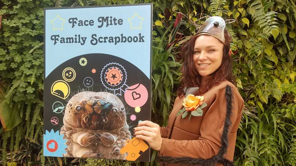 An educator dressed like a human face mite, with a large scrapbook of face mites