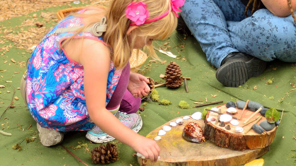 Girl making sculpture with found natural materials