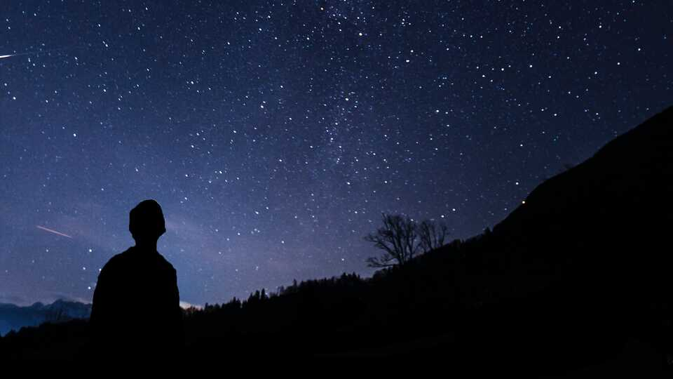 Silhouetted person looking up at dazzling night sky with stars