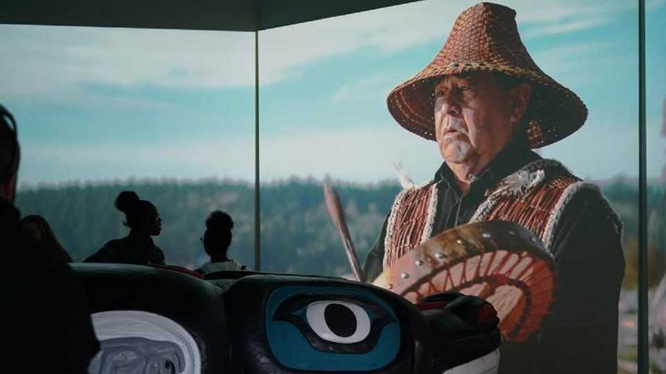 House of Tears Carver of the Lummi Nation pictured behind a carved totem, with guests observing