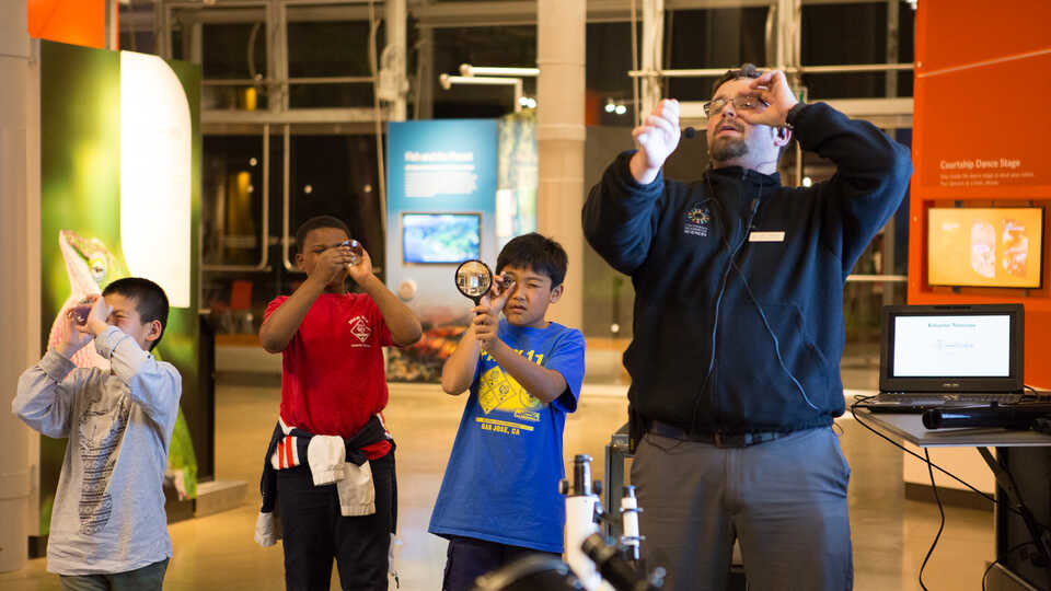 3 young guests practice proper hand lens technique with an Academy staff member